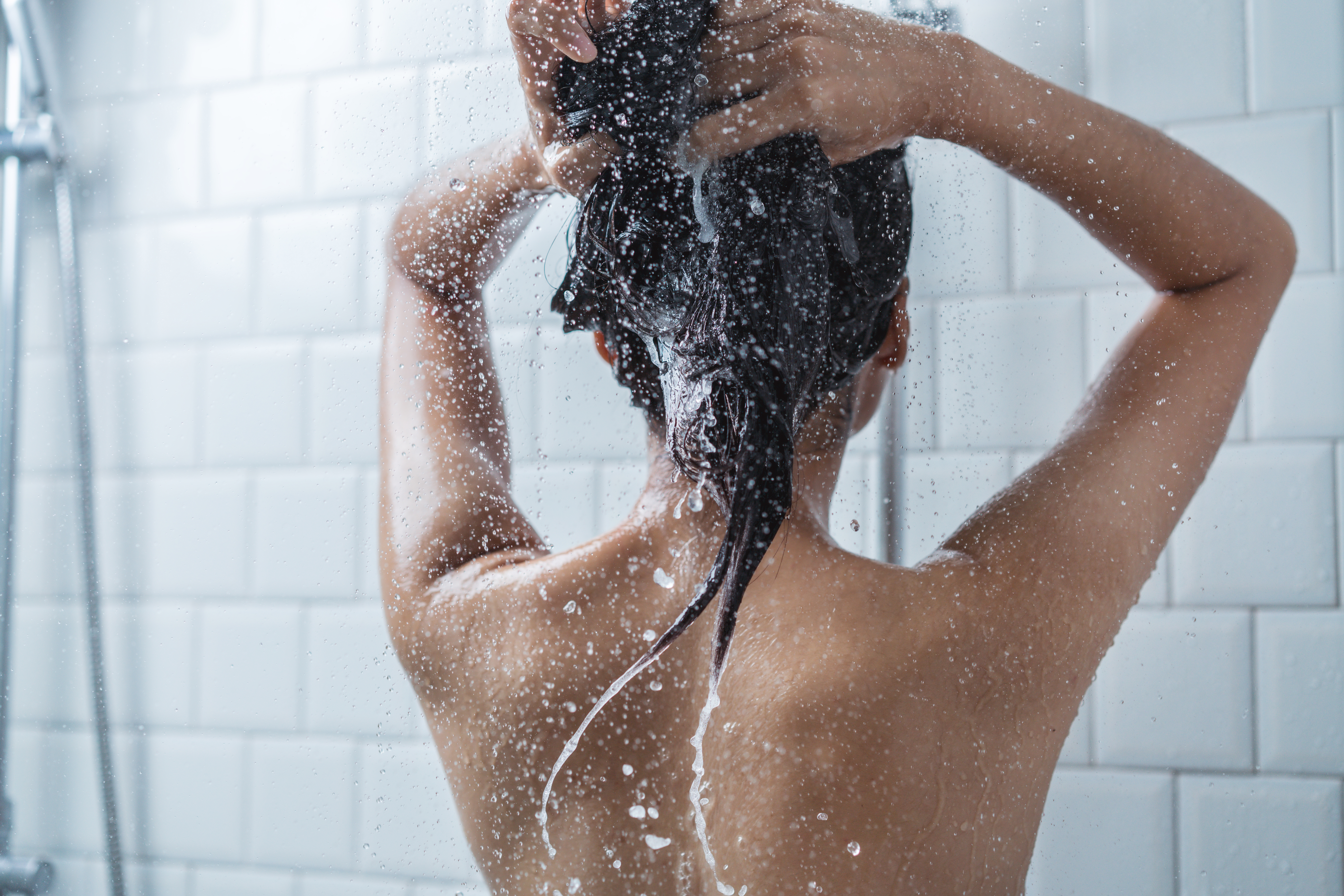 A tanned woman with her back to us in the shower, washing her hair with shampoo
