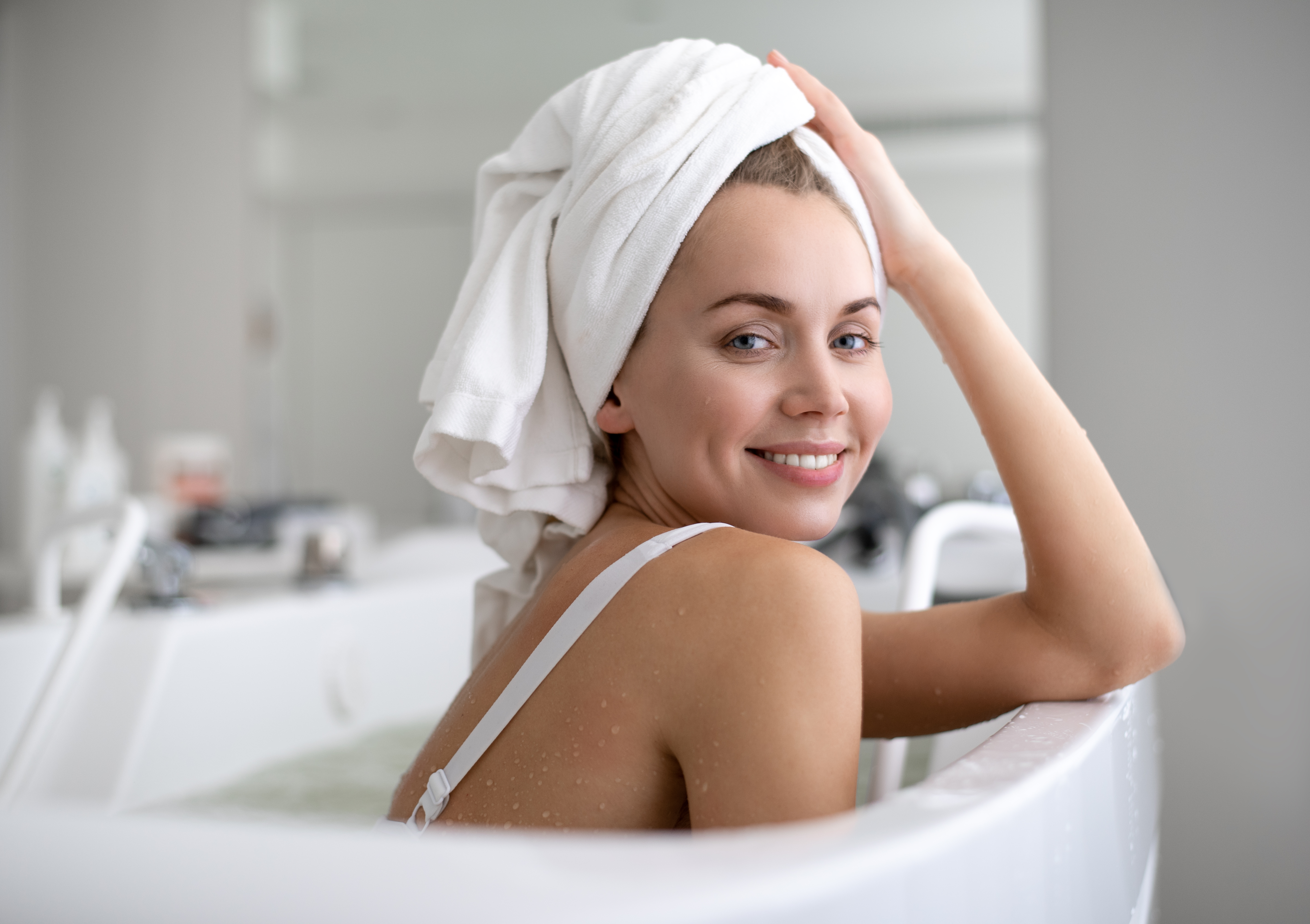 Woman sitting in the bath, smiling, with a white towel wrapped around her head